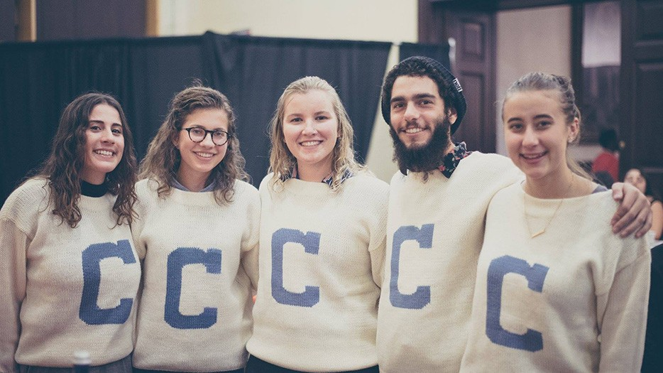 "Students in vintage-style crew letter sweater with a large ""C' gather for a Thanksgiving feast at John Jay Dining Hall in 2017. Photo courtesy of Columbia University Dining"