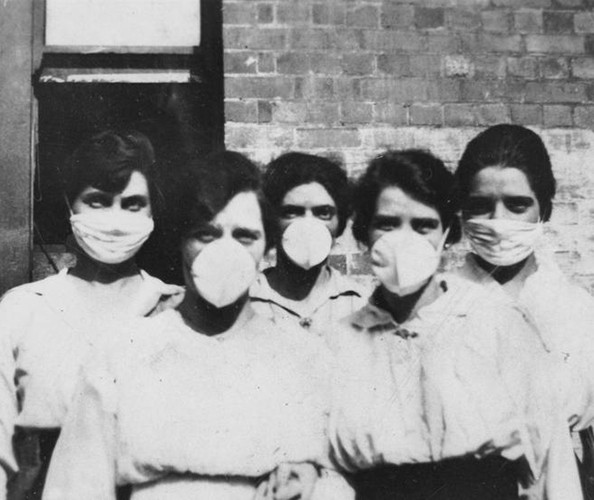 five women with black hair wearing white face masks and white shirts at turn of century