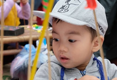 Asian toddler in white snoopy cap with grey sweatshirt