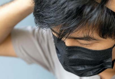 young asian man with tying on black mask