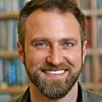 Headshot of Caucasian man with short brown hair and beard smiling with bookcases behind him