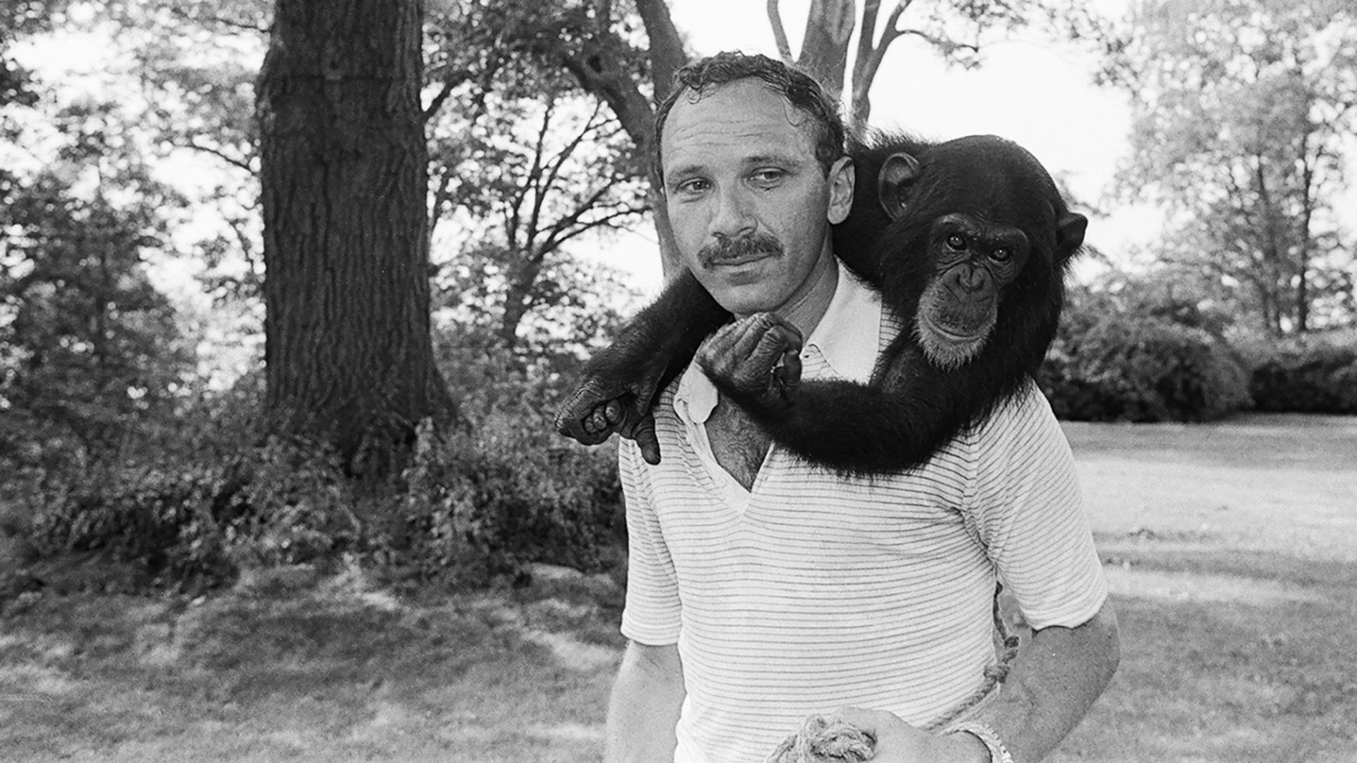 black and white image of young man with mustache carrying a chimp on his back