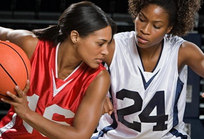 two  female black basketball players, one in red jersey holds orange ball; the other in white jersey tries to block her