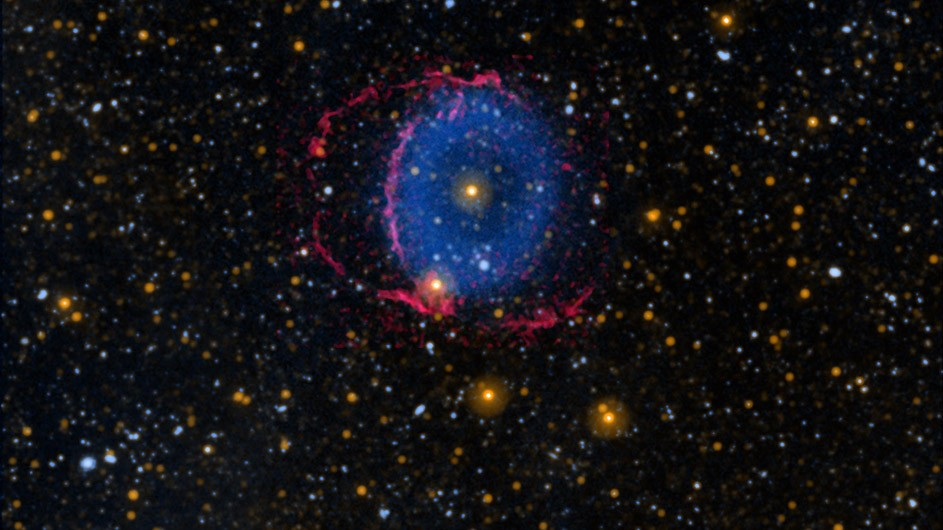 Black sky with hundreds of small stars and at center a blue donut-shaped ring with red lines surrounding it