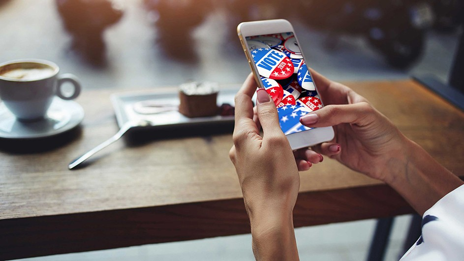 Hands hold a cellphone with image of red, white and blue VOTE buttons; a piece of cake with plate and spoon, plus white cup of expresso lies on a brown table
