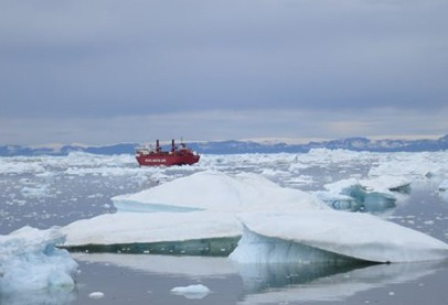 blue sky and icy ocean with icebergs and red ship