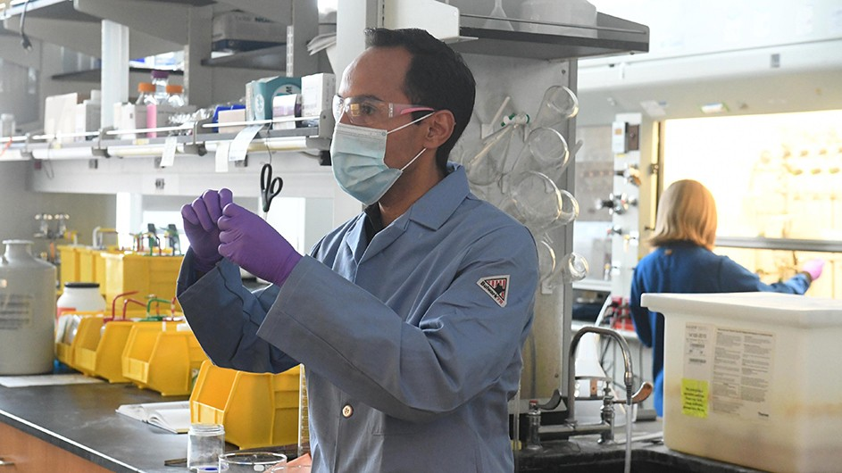 Dark-haired man in mask and safety goggles wearing purple gloves and blue shirt in lab with woman scientist back to him writing on white board