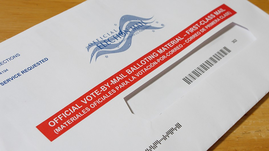 white letter with red stripe and in white letters it says Official Vote by Mail First Class. Black bar code below
