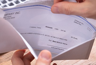 hands holding open paycheck in envelope