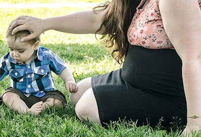 Pregnant mother in black skirt sitting on grass touching toddlers head
