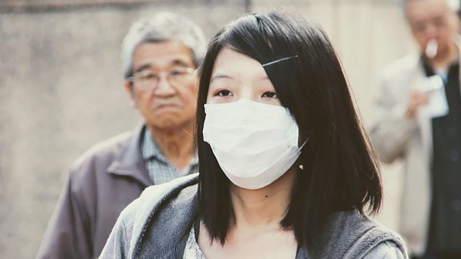 Woman with long black hair wearing white face mask. Older man with grey shirt and grey hair stands behind her