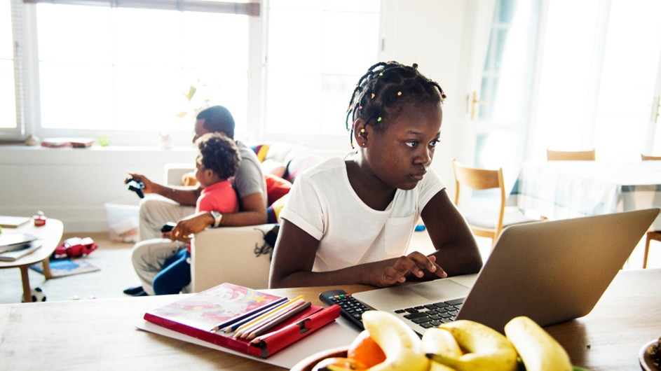 African American middle school aged girl with tight braids and white shirt on a laptop at a desk with father and younger brother (orange shirt) watching TV in background