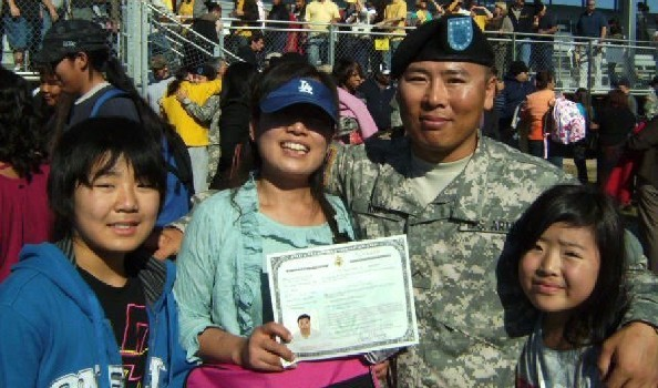 An Asian family of four with a woman in the center holding up a certificate next to a uniformed man