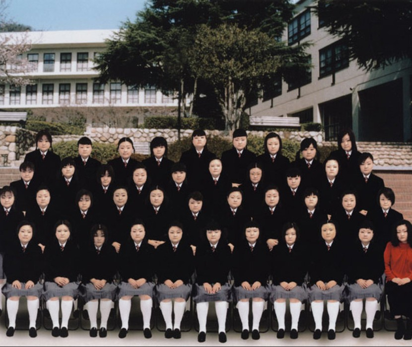 Rows of Asian school girls in uniform face the camera.