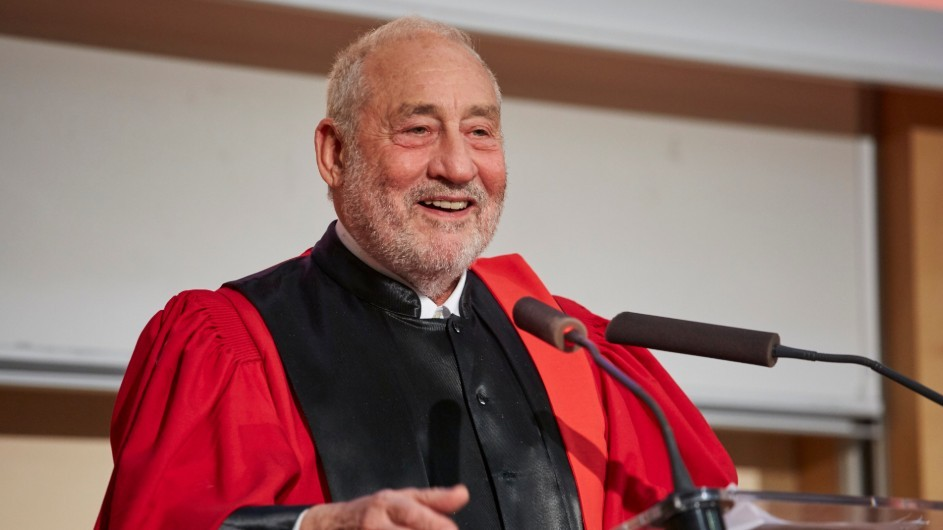 Joseph Stiglitz: a man with gray hair in black and red academic robes, smiling behind a podium