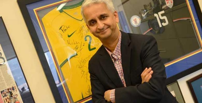 Sunil Gulati stands with arms folded smiling into camera wearing a dark blazer with red black and white plaid button down shirt