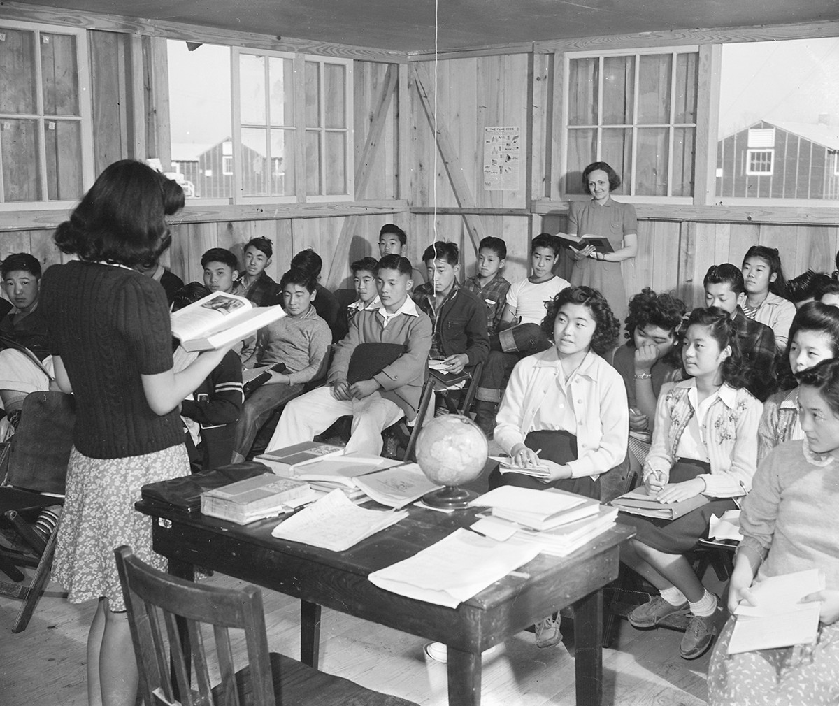 A teacher reads from a book in front of a classroom of children.