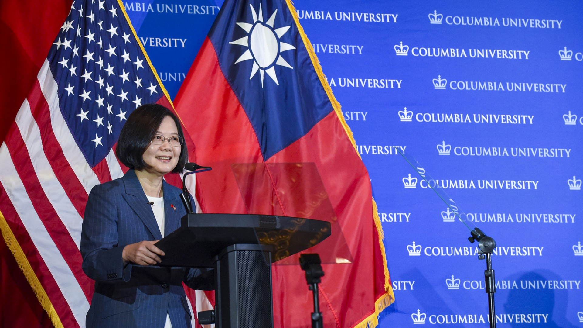 A woman wearing glasses standing in front of American and Taiwanese flags