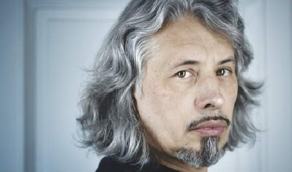 A man with goatee and long grey hair looking into the camera