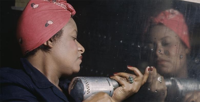 woman wearing a red bandana uses a powerdrill while working