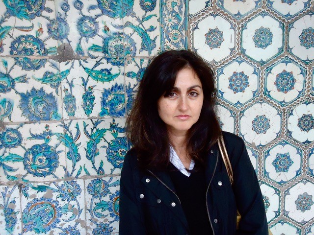 Zainab Bahrani against a blue patterned tiled background