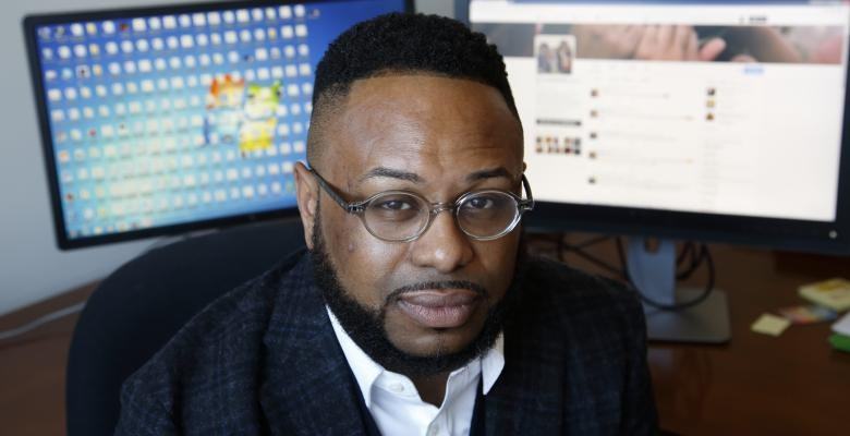 Desmond Patton looking directly into camera dressed in dark blazer white colored shirt.  Dark brown rimmed eyeglasses seated at 2 computer screens located behind him.