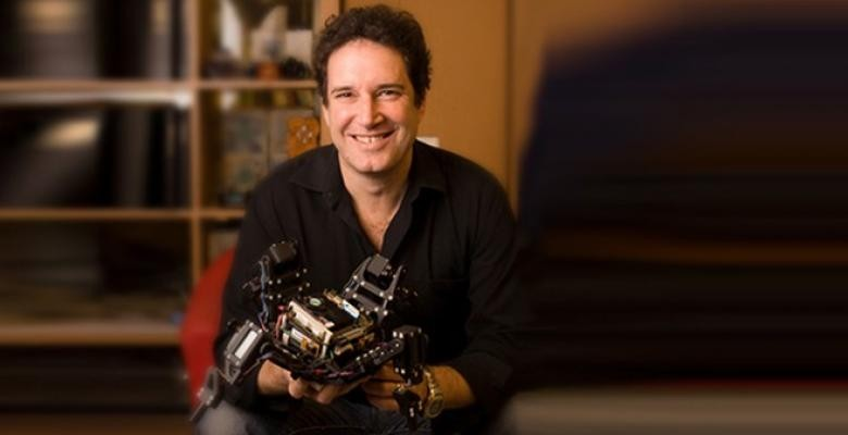 Prof. Lipson holding a hand held robot like machine