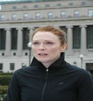 Actress Julianne Moore dressed in black sports jacket while hair is pulled back away from face.