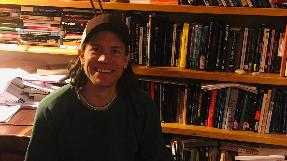 Justin Clarke-Doane: a man wearing a baseball cap sits in front of a desk with papers and full bookshelves.
