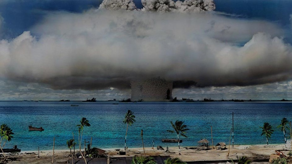 A fiery nuclear explosion over the blue water and palm trees of Marshall Island
