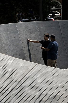"Two men look at a stone sculptured wall of the ""Memory Marks"" at the Memorial to Enslaved Laborers in Charlottesville, Va."