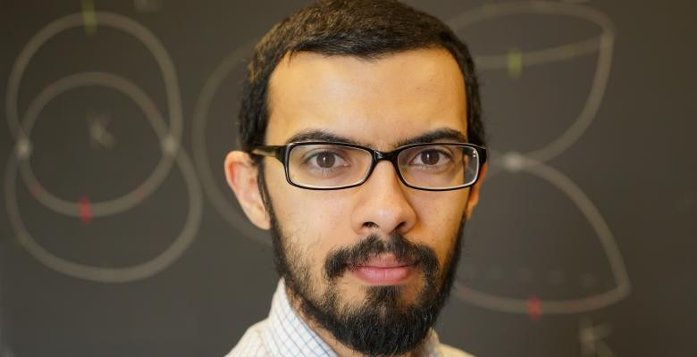 Columbia Mathematics Professor Mohammed Abouzaid wears dark rimmed eyeglasses dark facial hair covers jawline while he looks directly into camera