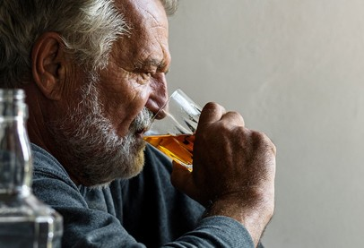 Older man with grey hair and beard drinking yellow liquid from glass with two bottles near him