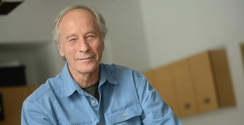 Richard Ford dressed in a blue denim shirt with brown shelves positioned on the wall in the rear