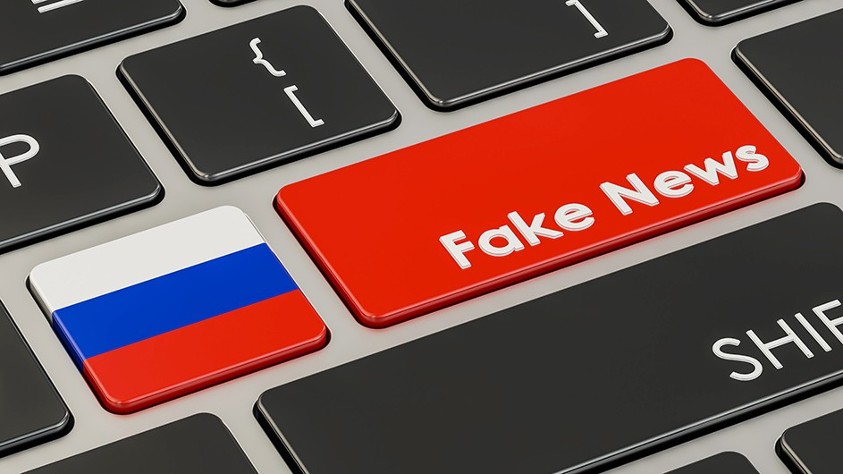 A detail of a computer keyboard with a red key that says Fake News next to a key with the Russian Federation flag (white, blue, and red stripes).