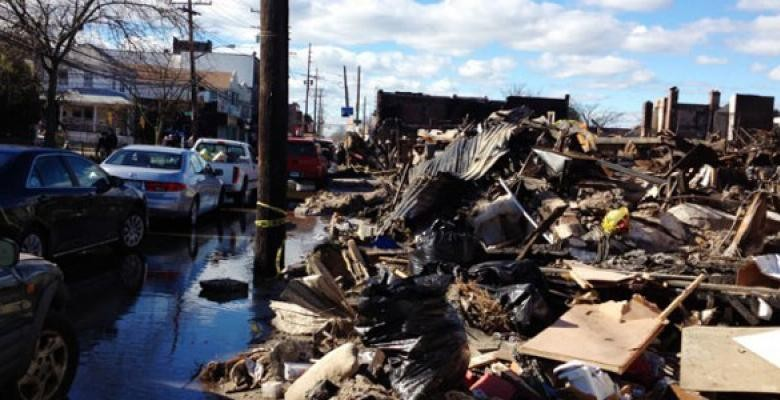 wreckage of buildngs and cars as a result of Hurricane Sandy with buildings in the far distance