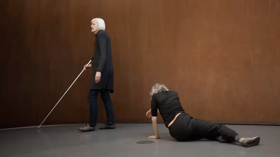 A woman with white hair and a cane walks behind a person leaning on the ground.