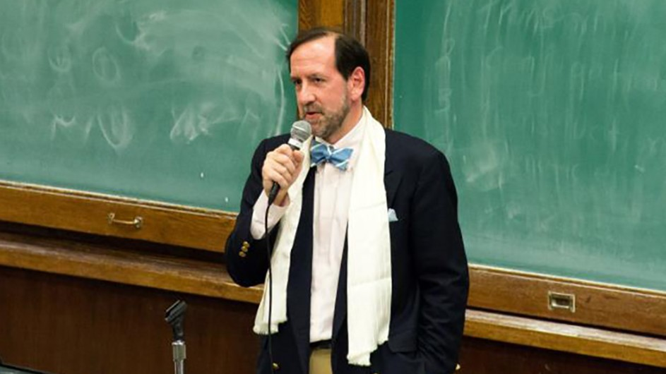 A man wearing a white scarf and dark jacket holds a microphone in front of green blackboards.