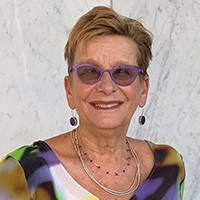 A photo of a woman wearing a colored shirt, jewelry and glasses.