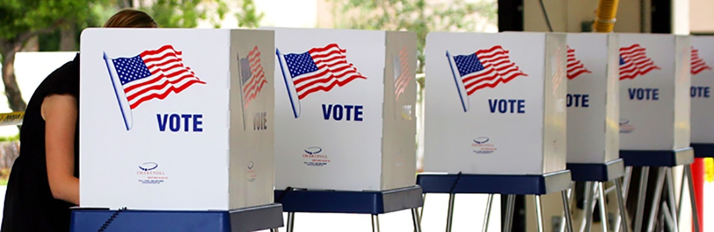 "A row of polling booths with American flags and the word ""Vote"" on them"