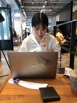 A woman with dark hair and a white shirt works at a laptop on a wooden surface.